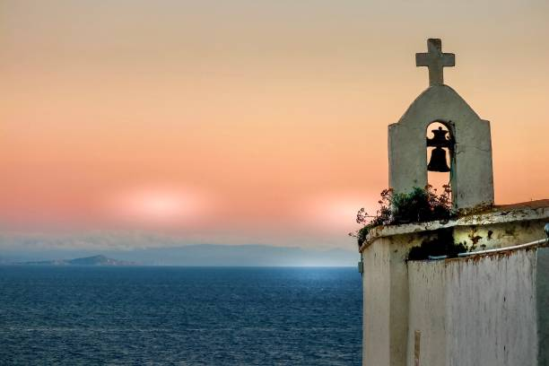 un clocher et sa croix en coucher de soleil sur la mer - josianne toubeix photos et images de collection