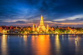 Long exposure photo of Wat Arun temple in front of Chao Phraya river in Bangkok at dusk. Thailand