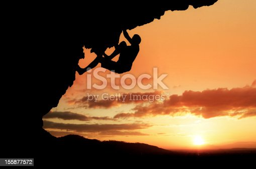 silhouette of free-climber in sunset on steep rock