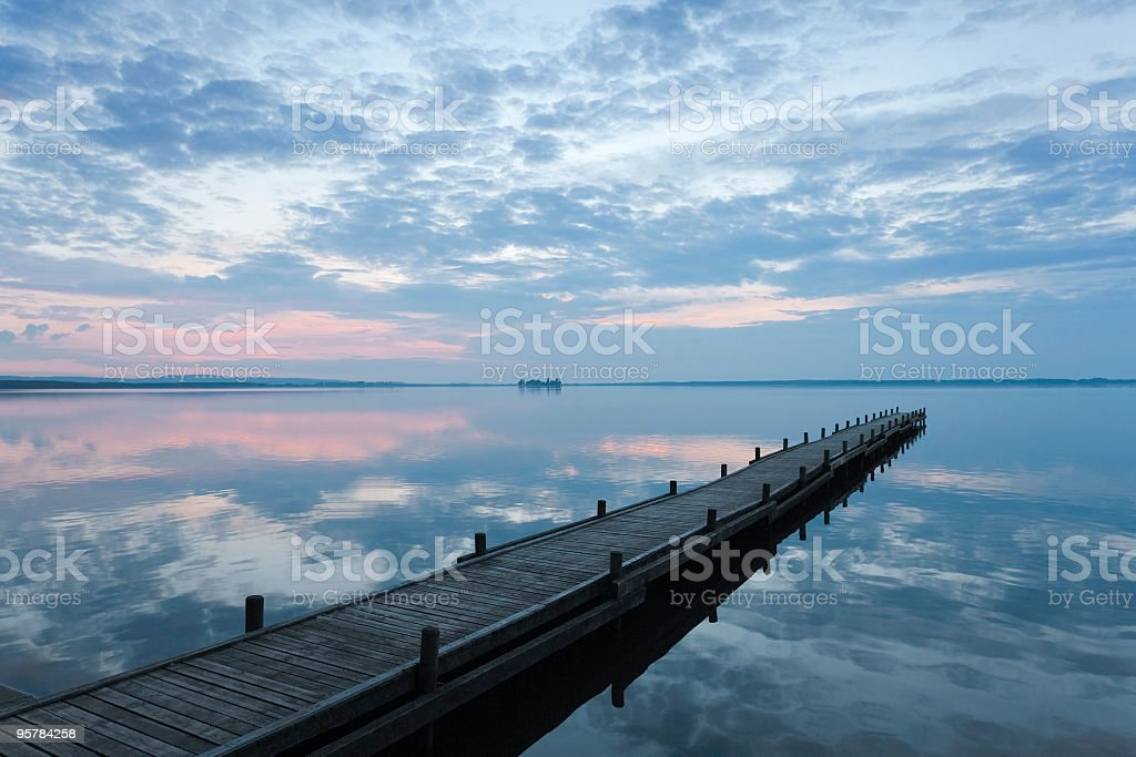 Sunset cloudscape reflection in lake with empty jetty (XL) stock photo