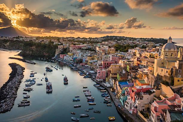 tramonto nuvoloso a porto corricella - procida foto e immagini stock