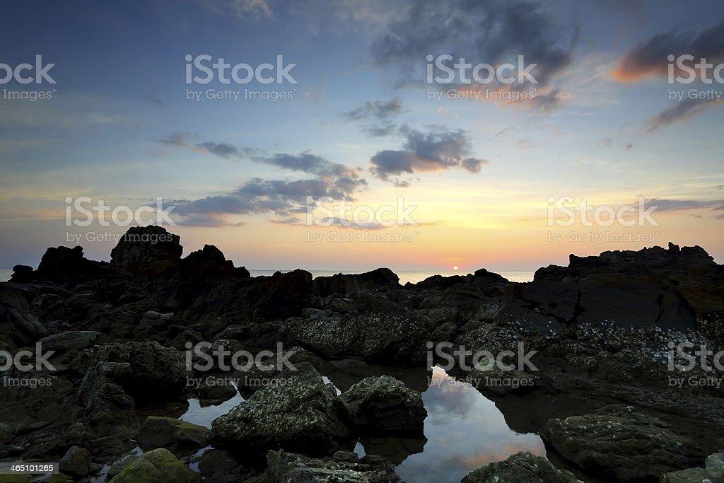 Sunset coast with rocks stock photo