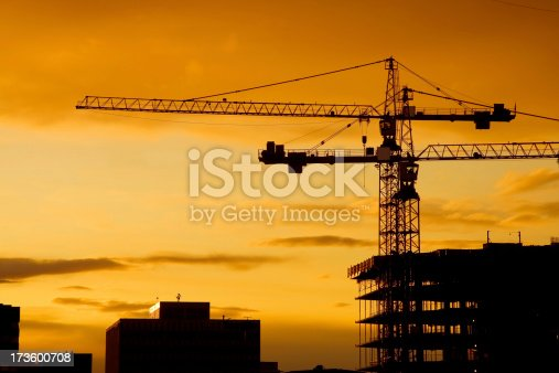 Two cranes sillouetted against a sunset sky