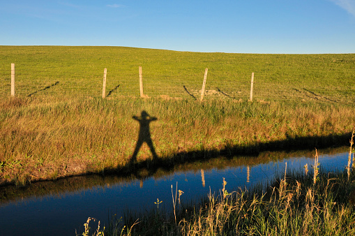 Sunset creates shadow of person along bank of irrigation canal in southern Alberta.