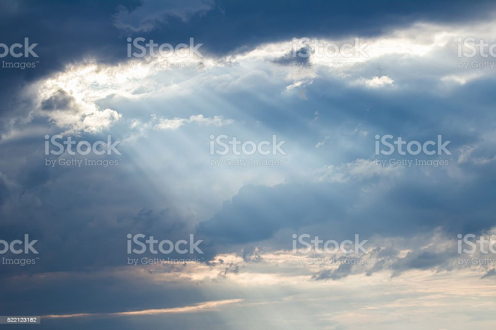 Sunset crepuscular rays pouring though scattered clouds stock photo