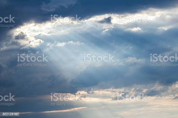 Photo of Sunset crepuscular rays pouring though scattered clouds