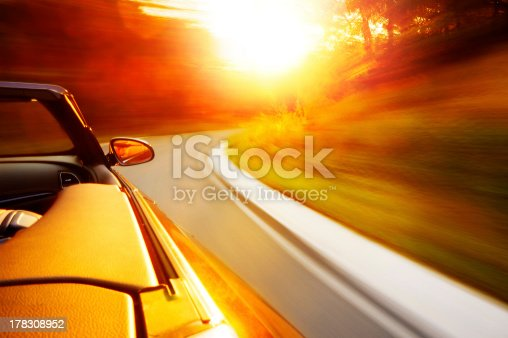 Motion blur shot of drive with a cabriolet in the sunset