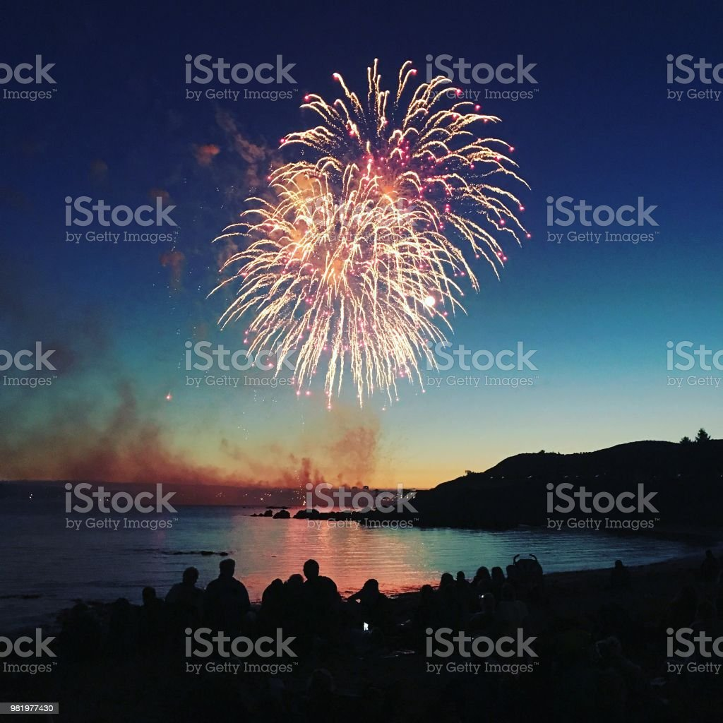 Sunset Firework over water People watching fireworks over the sea Celebration Stock Photo