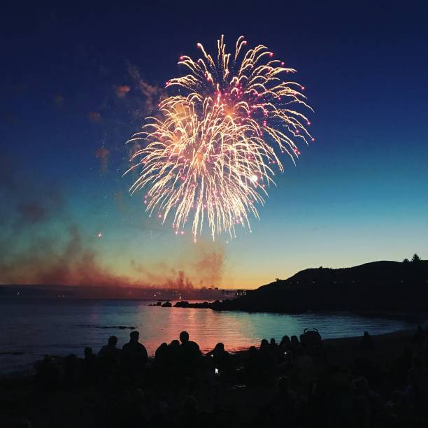 sunset firework over water - fireworks stock pictures, royalty-free photos & images