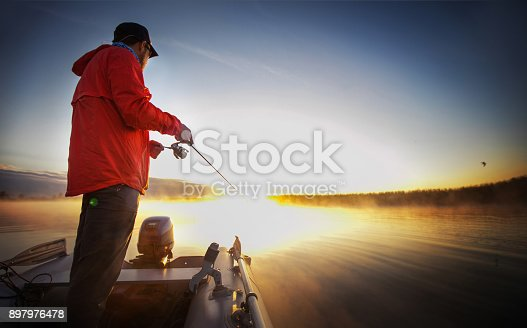 istock Sunset Fishing. Man fishing on a lake. 897976478