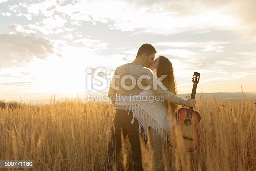Male guitarist and his girlfriend kissing in the middle of a prairie, enjoying a beautiful sunset outdoors.