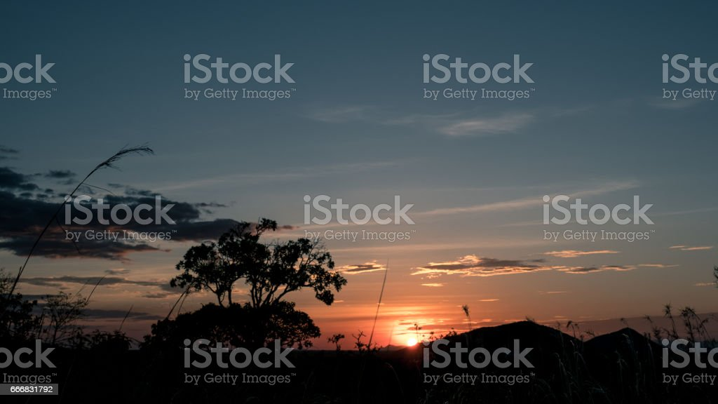 Sunset from afar in the meadows stock photo