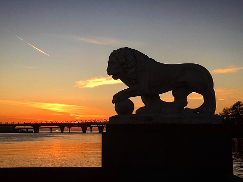 Sunset from the arrow of Elagin Island, the sun sets under the bridge to the Gulf of Finland. Lion sculpture