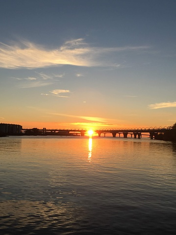 Sunset from the arrow of Elagin Island, the sun sets under the bridge to the Gulf of Finland.