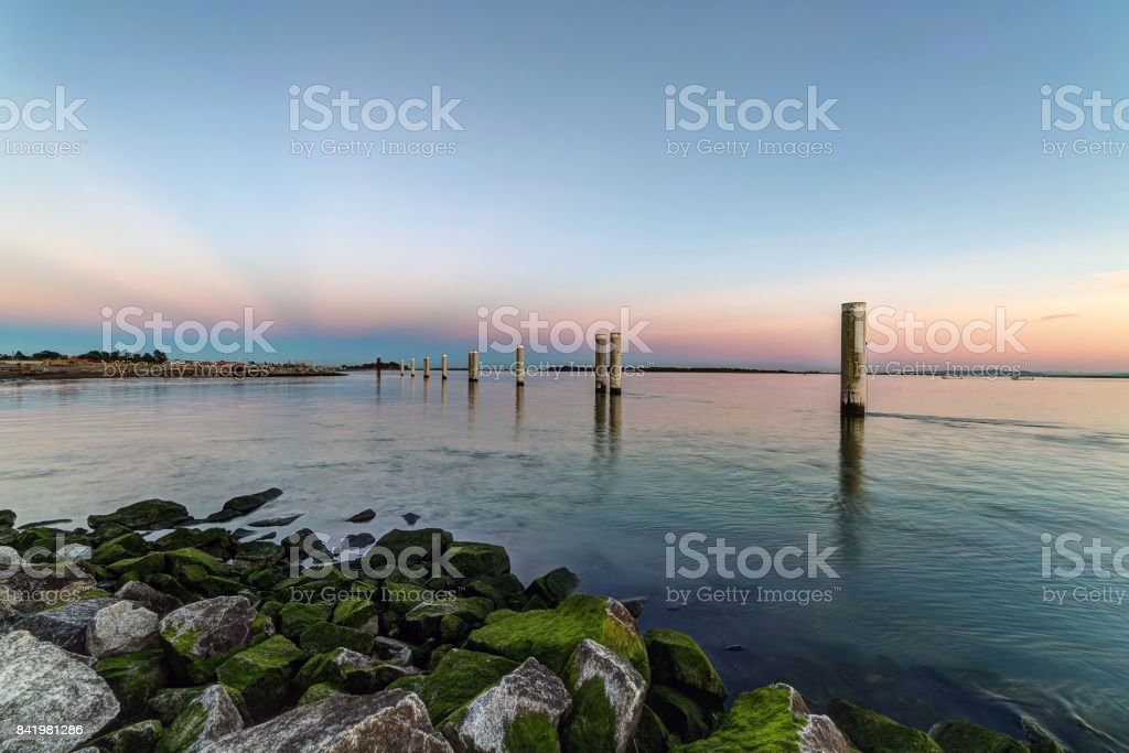 sunset glow over sea water with wooden poles stock photo