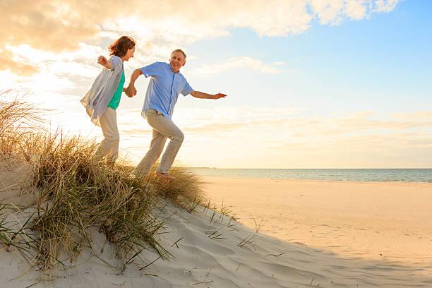 sunset-happy älteres paar am strand - wellness ostsee stock-fotos und bilder