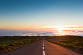 Highway through the beautiful nature down towards the atlantic ocean, leading into amazing cloudscape and sunset.