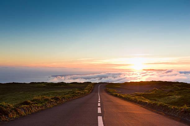 carretera en las nubes al atardecer - vía fotografías e imágenes de stock