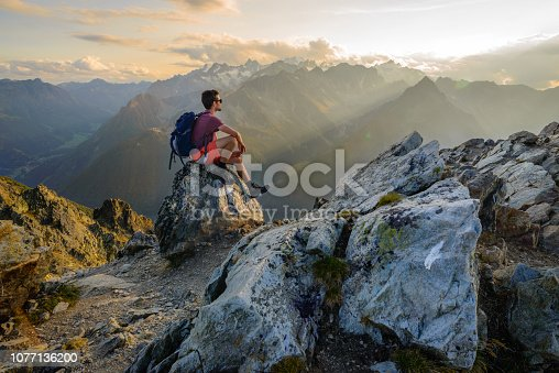 A man sitting on a rock at the summit of a mountain, admiring the scenery after a long hike.