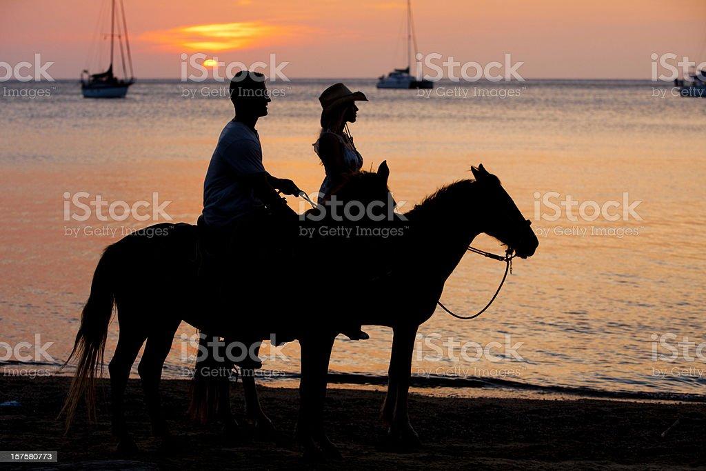 Sunset horseback ride on the beach royalty-free stock photo