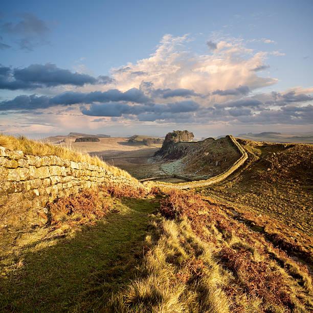 sunset illuminates hadrian's wall in northumberland, england - hadrian's wall stock-fotos und bilder