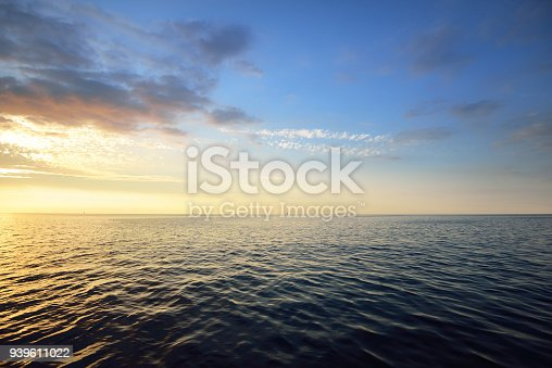 Sunset in a cloudy sky over open Baltic sea with veri distant ship silhouettes.
