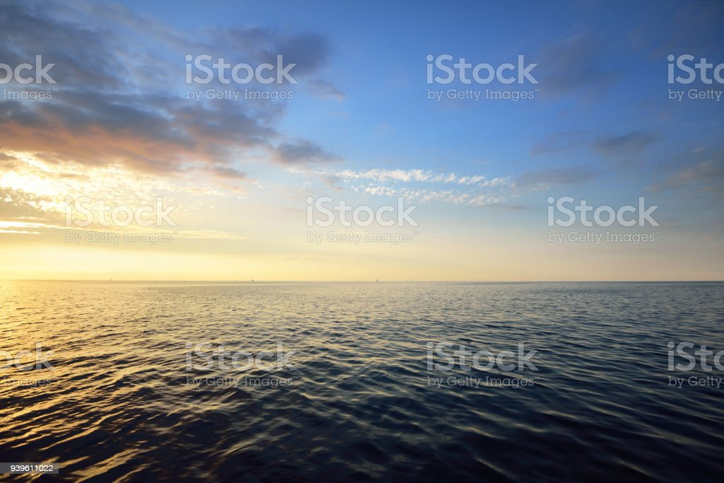 Sunset in a cloudy sky over open Baltic sea with veri distant ship silhouettes. stock photo