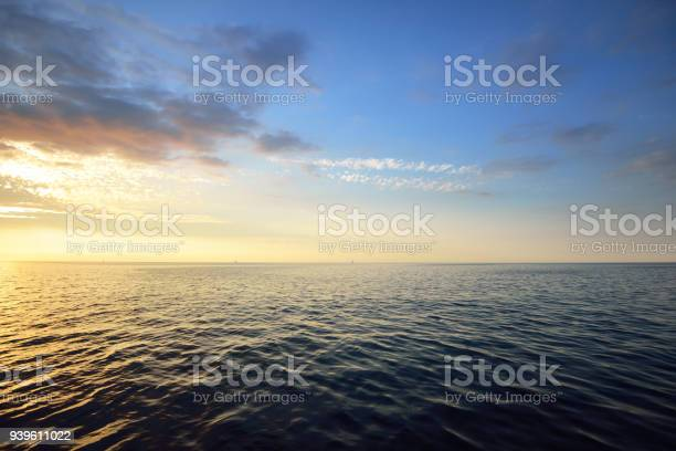 Photo of Sunset in a cloudy sky over open Baltic sea with veri distant ship silhouettes.