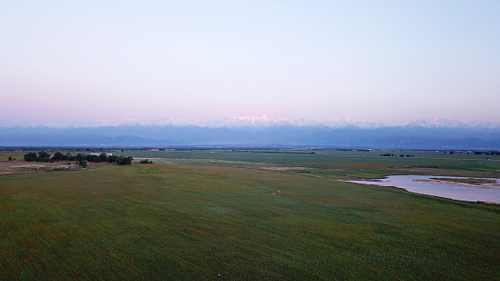 Sunset in a field with mountain and lake views. A green field with red poppies, a small lake in the distance. On the horizon, the orange rays of the sun fall on the snowy peaks of the mountains.