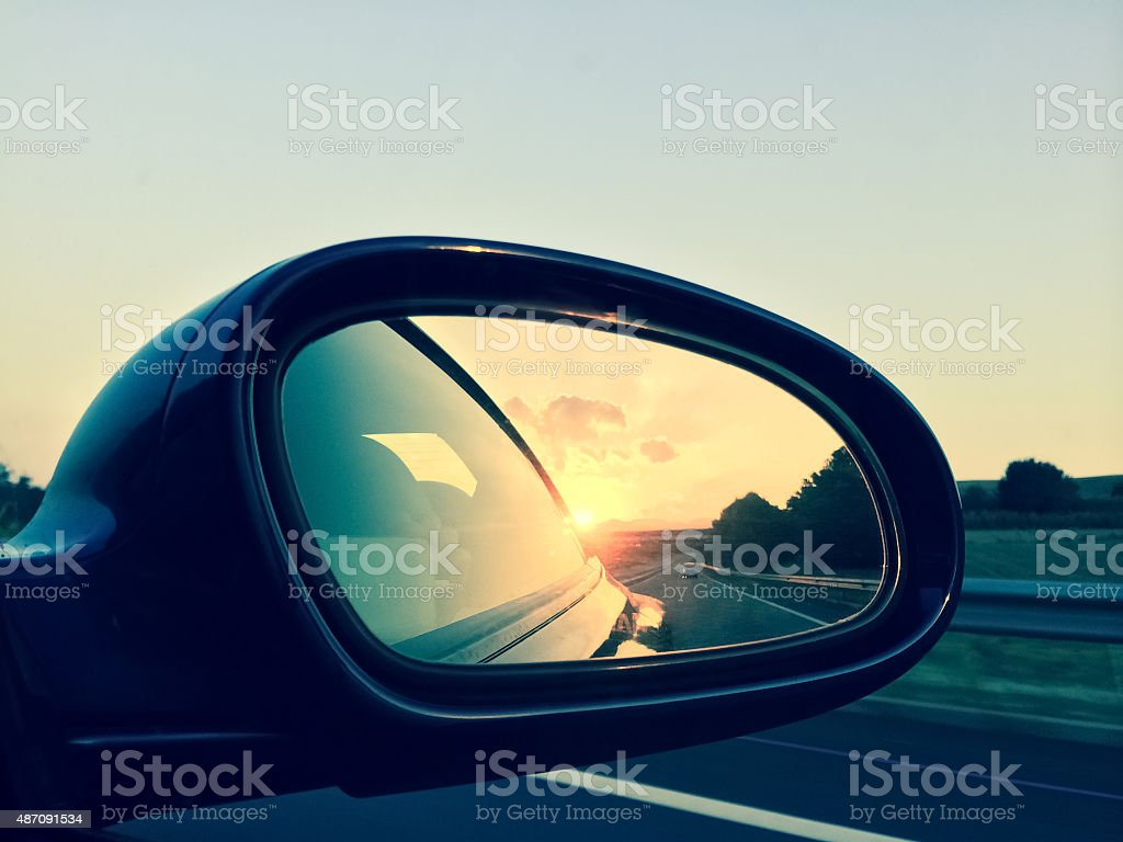 Sunset in a rear view mirror Sunset in a rear view mirror. Modern car on a highway. 2015 Stock Photo