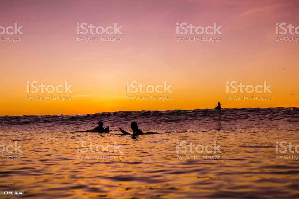 Sunset in Bali and surfers waiting for wave in ocean stock photo