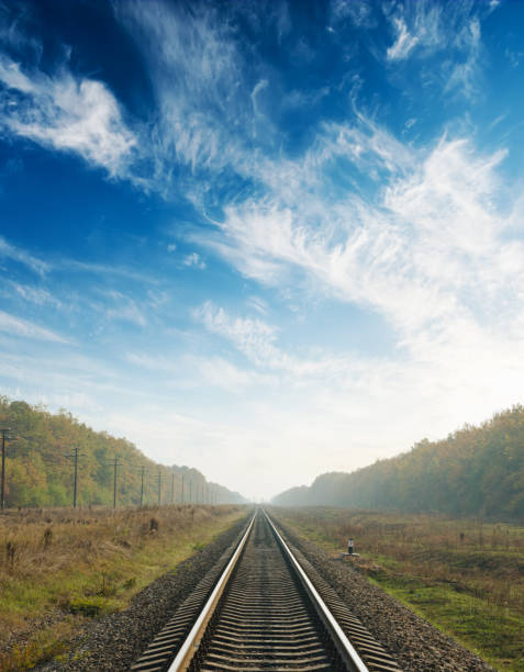 sunset in blue sky with clouds over railway to horizon sunset in blue sky with clouds over railway to horizon tramway stock pictures, royalty-free photos & images