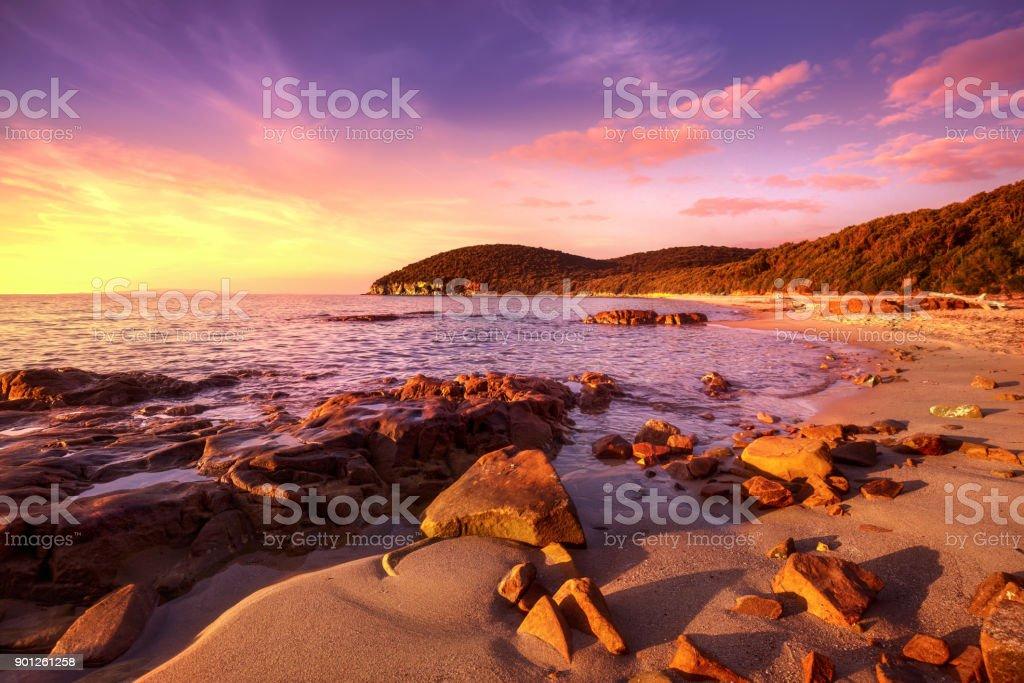 Sunset in Cala Violina bay beach in Maremma, Tuscany. Mediterranean sea. Italy. stock photo