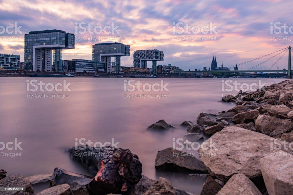 Sonnenuntergang in Köln am Rhein, Ausblick auf die Kranhäuser und den Kölner Dom mit Lila Wolken – Foto