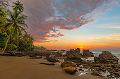 Sunset along the Pacific coast of Costa Rica with palm trees and rock formations inside Corcovado National Park, Osa Peninsula, Costa Rica.