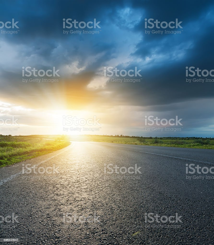 sunset in dark low clouds over asphalt road royalty-free stock photo