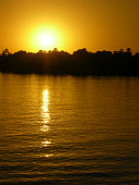 Sunset in Egypt on the Nile with palm trees in the background as a silhouette