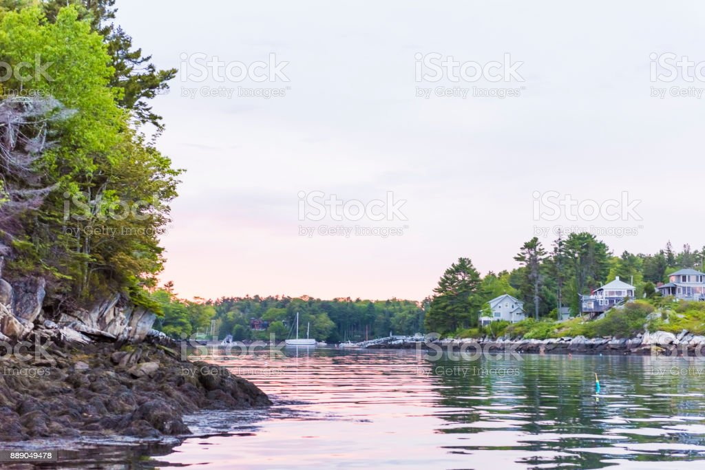Sunset in evening at Boothbay Harbor in small village in Maine with rocky coast and houses stock photo