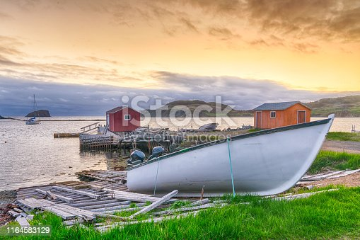 Boats and sheds in coastal fishing village during sunset in Newfoundland, Canada