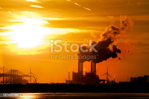Sunset in industrial area. Smokestacks from powerplant lit from behind.