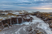 Sunset in Kailua Kona, Hawaii with lava rocks a waterfalls in the foreground