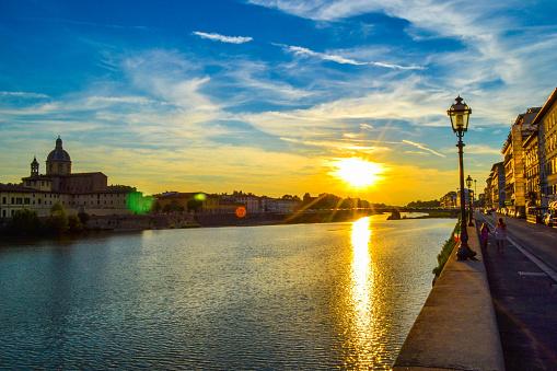 Sunset in Ponte Amerigo Vespucci (Amerigo Vespucci Bridge) through Arno river and San Frediano in Cestello (Church of Saint Fridianus) at the background, in Florence, Italy.