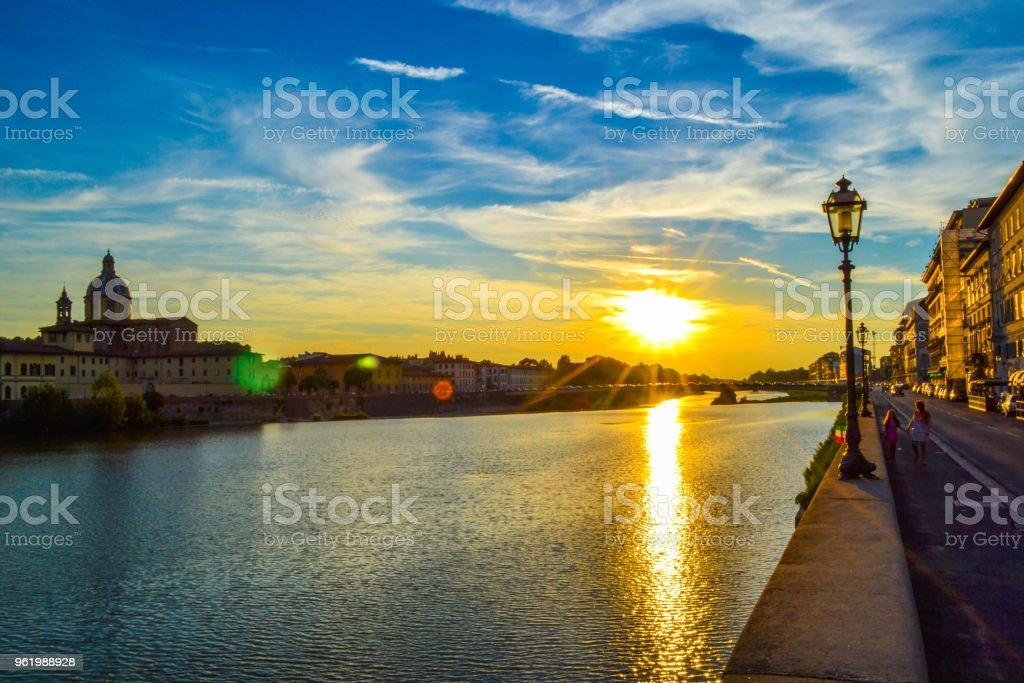 Sunset in Ponte Amerigo Vespucci (Amerigo Vespucci Bridge) through Arno river and San Frediano in Cestello (Church of Saint Fridianus) at the background, in Florence, Italy. - foto stock