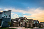 Real Estate Suburb New Development in Austin , Texas , USA - evening afternoon sunset bright sunshine on front yards and facade of new homes in Central Texas Neighborhood