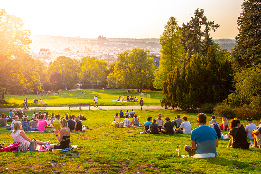 sunset in Rieger Gardens, Riegrovy sady, in Prague. Many people sitting in the grass and enjoying sunny summer evening and lookout of Prague historical city centre. Czech Republic