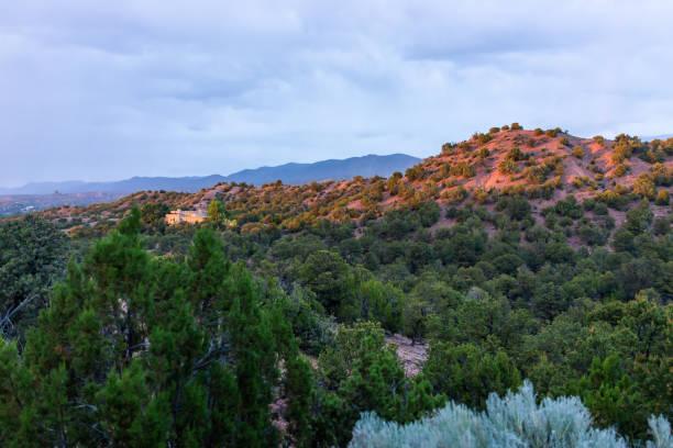 Por do sol em Santa Fe, montanhas de New Mexico no bairro da comunidade de Tesuque com casas, plantas verdes e o céu azul - foto de acervo