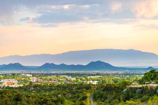 Sunset in Santa Fe, New Mexico skyline with golden hour light on green foliage summer plants and cityscape buildings with mountains silhouette stock photo