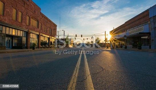 Storefronts at sunset in the middle of the road in downtown in a small Georgia town. The scene includes a low-angle view of the middle divider, sunburst at sunset, deep shadows and saturated colors.  The street and parking spaces are empty.