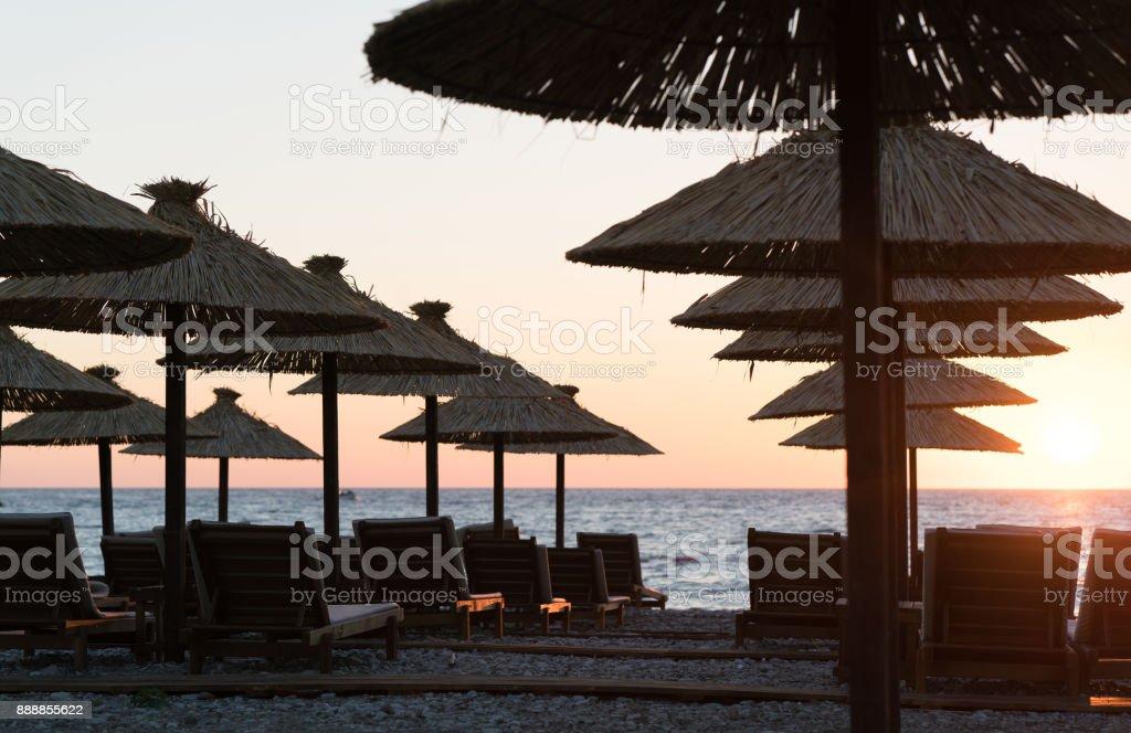 Puesta de sol en la ciudad costera de barra con siluetas de sombrillas en la playa - foto de stock