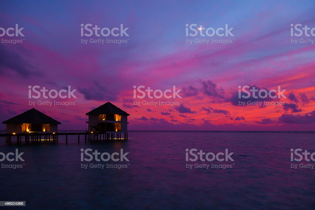 Sunset in the Maldives with a view of the bungalows Stunning sunset on the island Rannalhi, Maldives. The sky is filled with warm colors. 2015 Stock Photo
